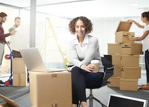 female business woman surrounded by moving boxes