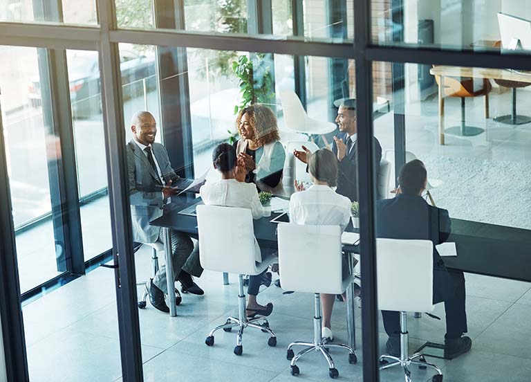 business people gathered around conference table clapping