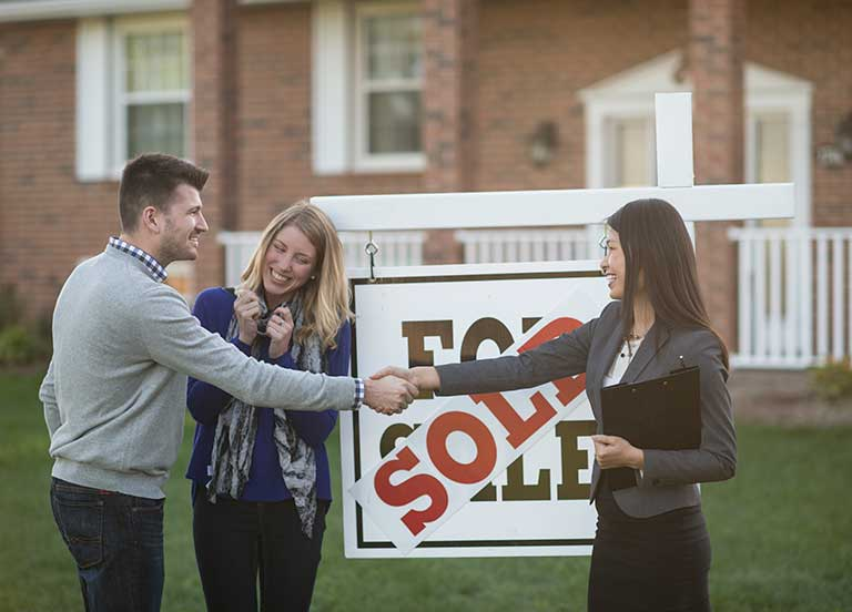 couple-shaking-hands-with-realtor-in-front-of-sold-home