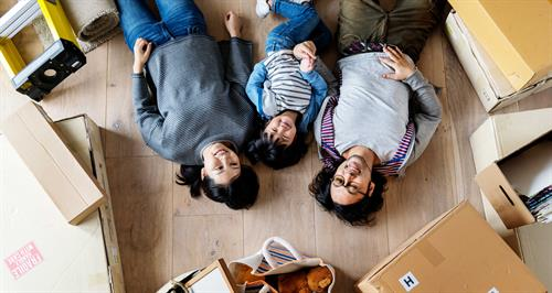 family lies on floor with moving boxes