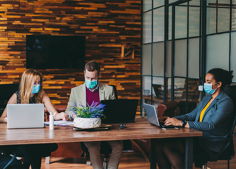 business people wearing masks sitting at a table