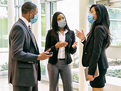 professional-coworkers-wearing-masks-mid-discussion