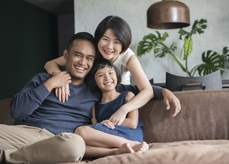 Young parents with child sitting on the sofa